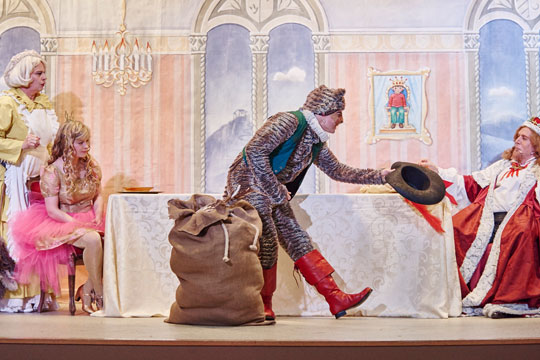 Chammerjungfere (Rosie von Holt) und Prinzässli Abigstärn (Isabel Sulger Büel) freuen sich über den Besuch vom Diener des Grafen Carabas, Herr Philias von Schnurr (Reto Ziegler). Auch König Melchior XXII. (Lukas Schönenberger) freut sich, der Besucher überreicht ihm ein Geschenk.