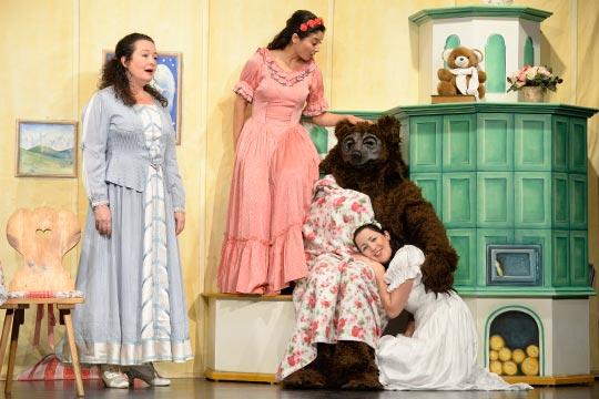 Muetti (Nicole Haas-Clerici) singt zusammen mit ihren Töchtern Schneewiissli (Diana Spadarotto) und Roserot (Camilla Gomes dos Santos) ein Gut-Nacht-Lied für ihren Gast, den Bären (Marc Hofmann).