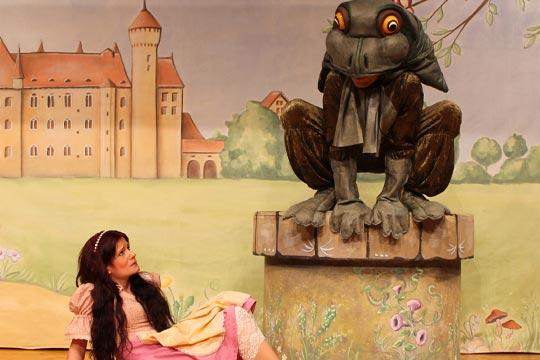 Prinzässli Tuusigschön (Christine Strasser) erschrickt, als aus dem Brunnen plötzlich ein grosser Frosch (Rafael Beutl) auftaucht.