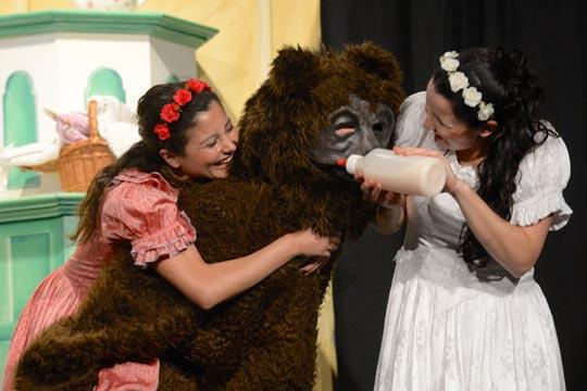 Roserot (Camilla Gomes dos Santos) und Schneewiissli (Diana Spadarotto) verabreichen dem Bären (Marc Hofmann) einen Honigmilch-Schoppen. Mhhmm!