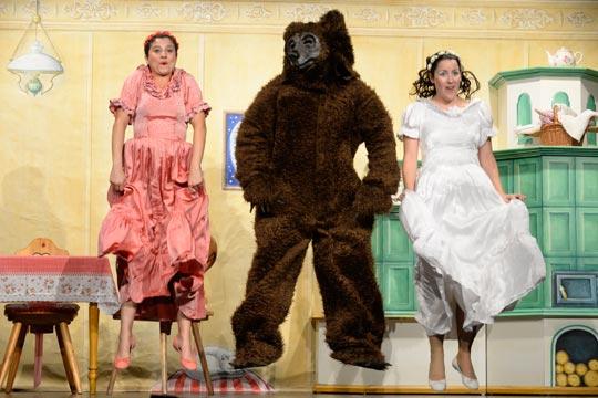 Roserot (Camilla Gomes dos Santos) und Schneewiissli (Diana Spadarotto) freuen sich, dass sie zusammen mit dem Bären (Marc Hofmann) lustige Spiele und Tänze machen können.