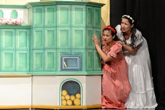 Als es plötzlich klopft, erschrecken Roserot (Camilla Gomes dos Santos) und Schneewiissli (Diana Spadarotto), sie verstecken sich hinter dem Ofen.