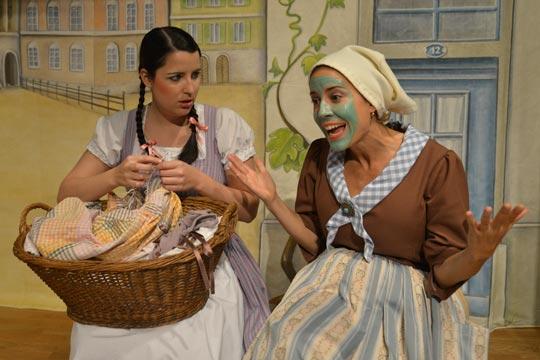 Rosmarie (Diana Spadarotto) macht die ganze Arbeit, während sich Mutter Bluemer (Claudia Mai) auf das Kafichränzli vorbereitet und mit ihr schimpft.