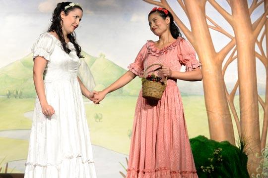 Schneewiissli (Diana Spadarotto) sammelt mit Roserot (Camilla Gomes dos Santos) Waldbeeren. Sie freuen sich, dass sie ihrer Mutter so ein feines Dessert nach Hause bringen können.