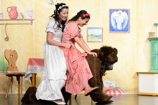 Schneewiissli (Diana Spadarotto) und Rosenrot (Camilla Gomes dos Santos) lassen sich auf dem Rücken vom Bären (Marc Hofmann) durch die ganze Stube tragen.